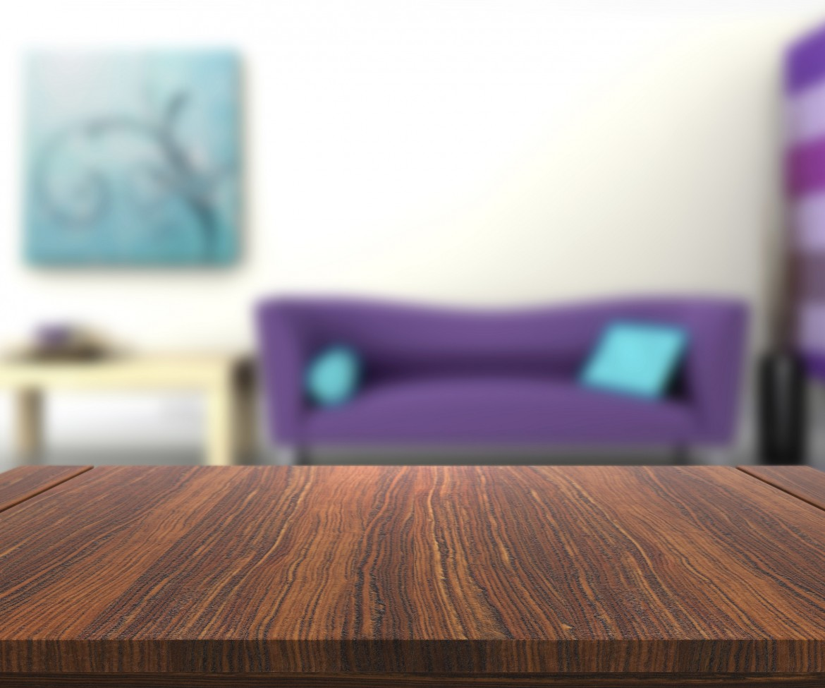 3D render of a wooden table with a defocussed modern lounge in the background
