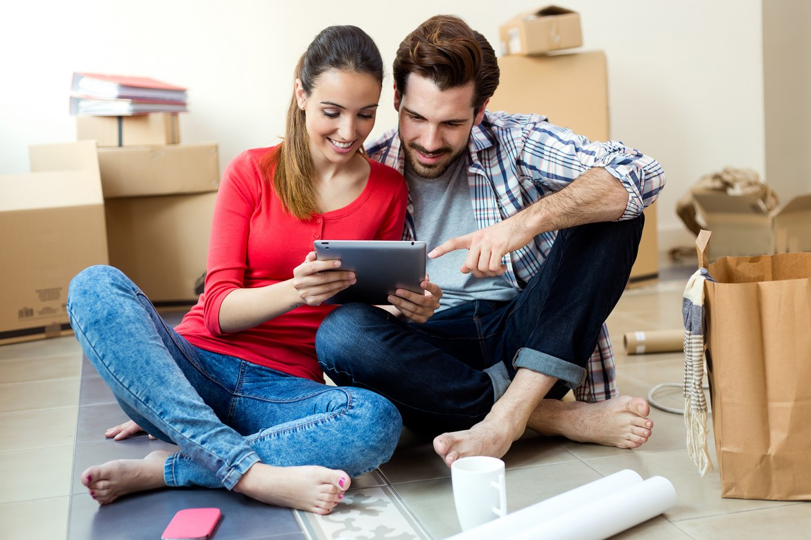 Portrait of Young couple with digital tablet in their new home