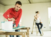 Pareja pintando su casa